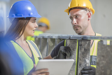 Woman with tablet talking to man with ladder on construction site - ZEF15369
