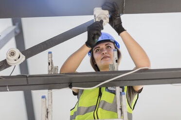 Young female electrician installing lamp - ZEF15372