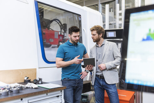 Two men with tablet talking in modern factory - DIGF03816