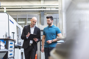 Businessman and employee with clipboard in modern factory - DIGF03825