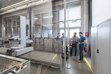 Two men looking at machine in modern factory - DIGF03828