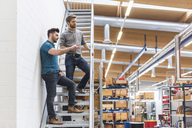 Two men talking in factory storehouse - DIGF03837
