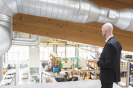Businessman with tablet in modern factory looking at shop floor - DIGF03840