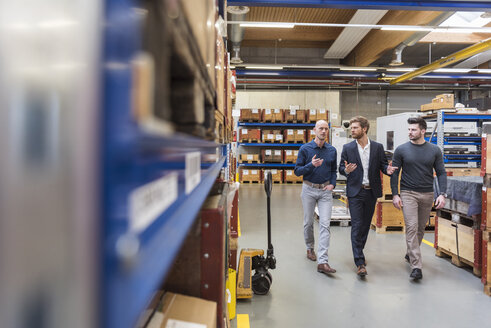 Three men walking and talking in factory storeroom - DIGF03849