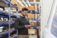 Man examining product in factory storeroom - DIGF03858