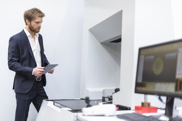 Businessman with tablet looking at machine in modern factory - DIGF03861