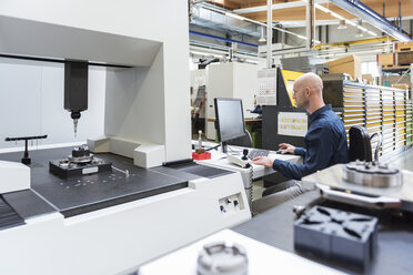 Man using computer at machine in modern factory - DIGF03864