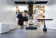 Man examining machine in modern factory - DIGF03867