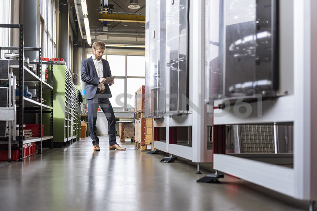 Businessman using tablet in modern factory - DIGF03879