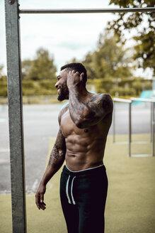 Tattooed bodybuilder standing on sports field - DAWF00592