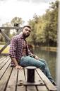 Portrait of muscular man sitting on jetty - DAWF00604