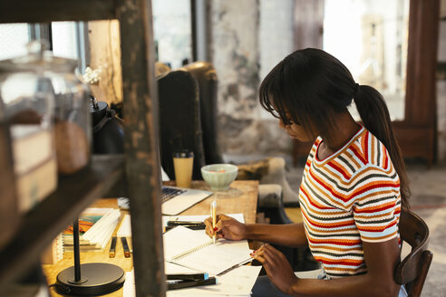 Young woman working at desk in a loft - EBSF02275