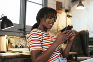 Portrait of smiling young woman sitting in a loft using cell phone - EBSF02287