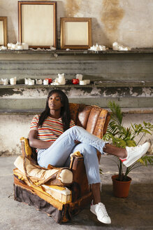 Portrait of cool young woman sitting on an old leather chair in a loft - EBSF02296