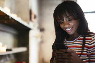 Portrait of smiling young woman using cell phone - EBSF02305