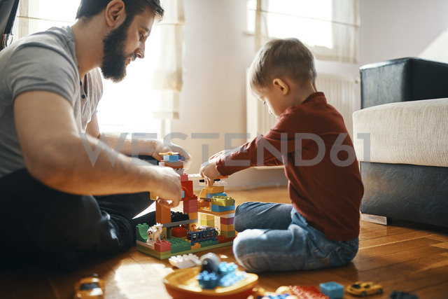 Father and son sitting on the floor  playing together with building bricks - ZEDF01276 - Zeljko Dangubic/Westend61