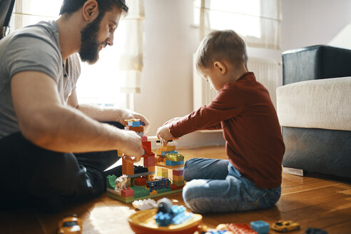 Father and son sitting on the floor  playing together with building bricks - ZEDF01276