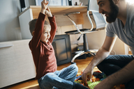 Father and son sitting on the floor at home playing together with building bricks - ZEDF01279