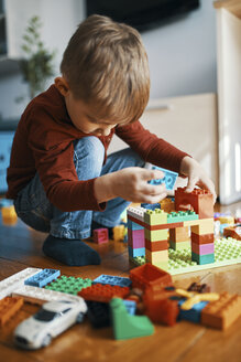 Little boy playing with building bricks on the floor at home - ZEDF01282