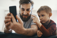 Portrait of father and little son with smartphone - ZEDF01294