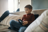 Portrait of little boy sitting on the couch playing computer game - ZEDF01297