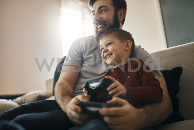 Happy father and little son sitting together on the couch playing computer game - ZEDF01300 - Zeljko Dangubic/Westend61