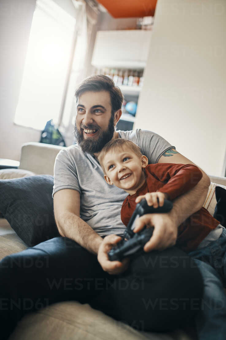 Laughing father and little son sitting together on the couch playing computer game - ZEDF01303 - Zeljko Dangubic/Westend61