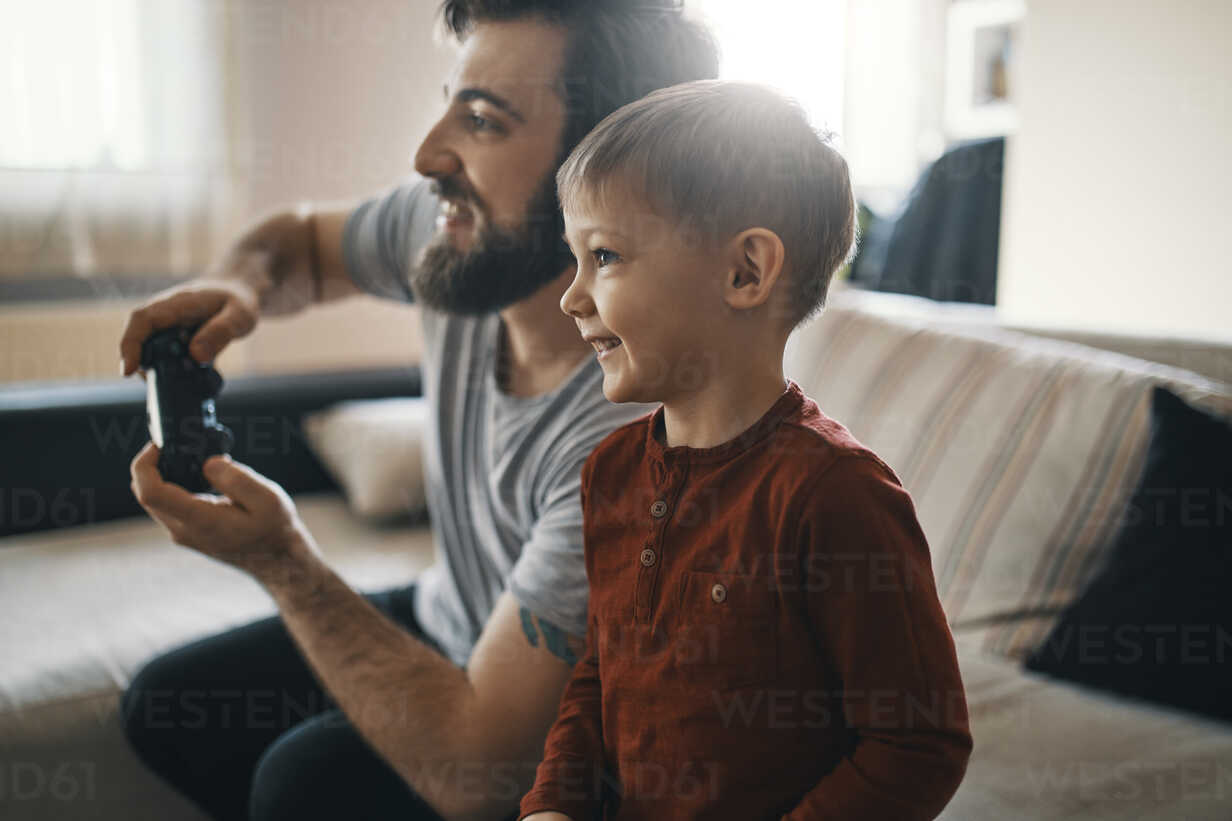 Happy little boy playing computer game with his father at home - ZEDF01306 - Zeljko Dangubic/Westend61