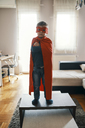 Little boy dressed up as a superhero standing on coffee table at home - ZEDF01312