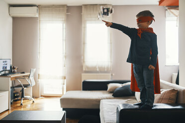 Little boy dressed up as a superhero standing on coffee table at home pointing on something - ZEDF01315