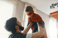 Father playing with his little son dressed up as a superhero - ZEDF01321