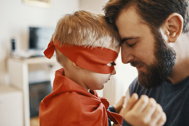 Little boy dressed up as a superhero head to head with his father - ZEDF01324