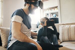 Father and little son sitting on the couch at home wearing virtual reality glasses - ZEDF01327