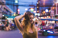 Thailand, Bangkok, young woman in the city on the street at night - AFVF00383