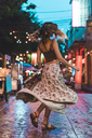 Thailand, Bangkok, young woman in the city dancing on the street at night - AFVF00386