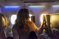 Young woman in plane at sunrise - AFVF00395