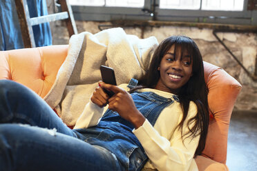 Portrait of smiling woman lying on the couch at home using cell phone - EBSF02309