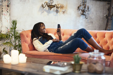 Laughing woman lying on the couch at home using cell phone - EBSF02315
