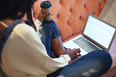 Young woman sitting on the couch with coffee to go using laptop - EBSF02324