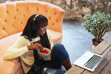 Laughing young woman sitting on the floor of her loft using laptop and headphones - EBSF02333