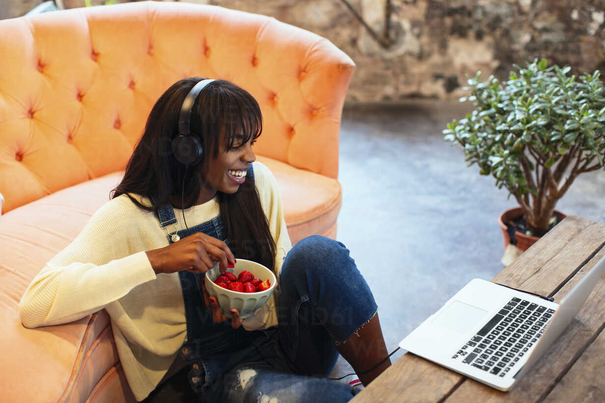 Laughing young woman sitting on the floor of her loft using laptop and headphones - EBSF02333 - Bonninstudio/Westend61