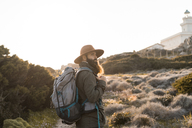 Italy, Sardinia, hiker with hat and backpack watching something - AFVF00401