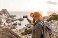 Italy, Sardinia, hiker with hat and backpack taking photo of the sea with cell phone - AFVF00410