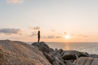 Italy, Sardinia, man standing on rock at sunset looking at view - AFVF00413
