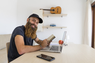 Portrait of bearded young man sitting at desk with laptop and notebook - AFVF00425