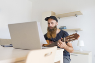 Serious young man at home with earphones and laptop playing guitar - AFVF00431