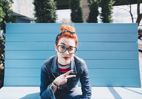 Portrait of redhead young woman gesturing peace sign while sitting on bench - MASF01365