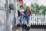 Portrait of hipster female friends standing against fence by building - MASF01368