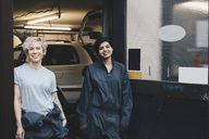 Portrait of smiling female mechanics standing at doorway of auto repair shop - MASF01371