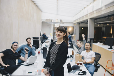 Portrait of happy female computer programmer with colleagues sitting at desk in background - MASF01374